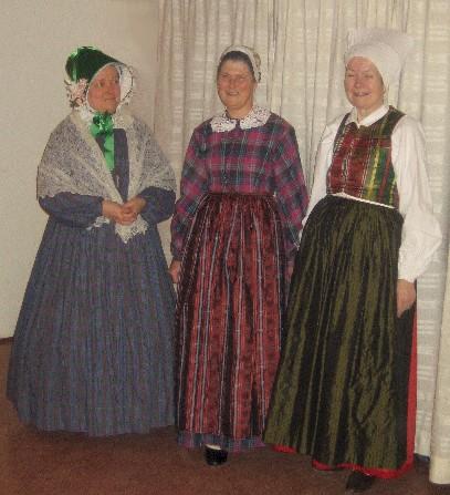 825919578b18 ... i mitten kvinna i klänning av modernt snitt (men utan krinolin) men  fortfarande med bondkvinnans typiska bindmössa och förkläde, t.v. kvinna i  djärvt ...